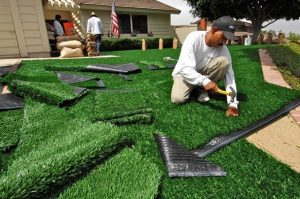Image of an man doing Artificial turf is a surface of synthetic fibers made to look like natural grass.
