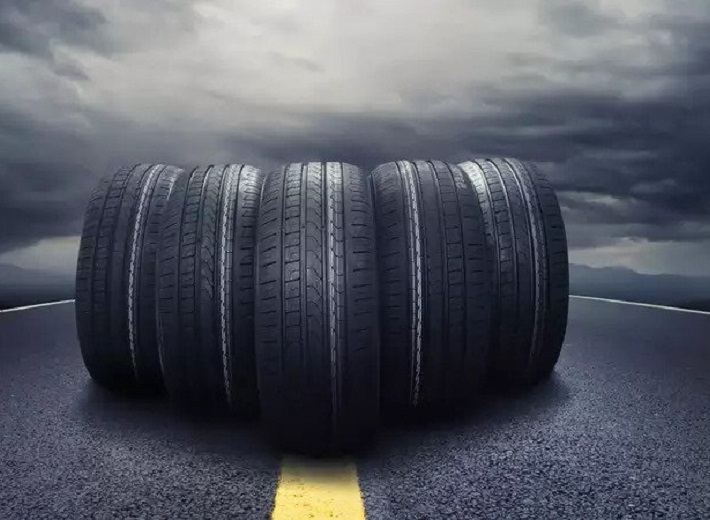 Image of Car tires close-up wheel placed on the road on dusky cloud background.