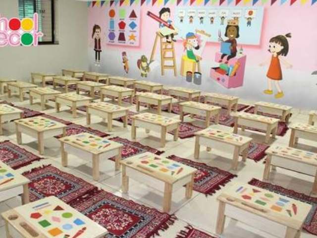 Preschool Classroom Interior With Multiple Drawing Tables & Colorful Drawings On The Wall.